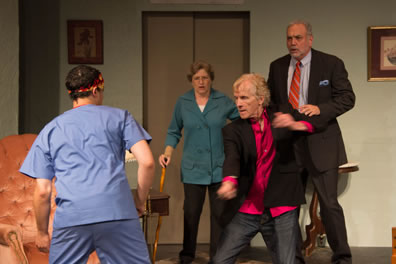 Mercutio, back to us, in blue nurses outfit and Aztec head band, Benvolio in thigh-length turquoise shirt and black pants and leaning on a cane, Tybalt in open sport jacket, bright chartreuse shirt and jeans, and Romeo in suit and tie with blue shirt. In the background, a gold easy chair, the elevator, and paintings on the wall.