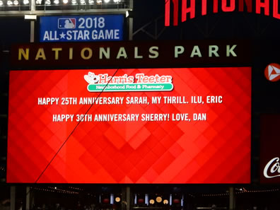 "Nationals Park scoreboard, red background, Harris-Teeter Neighborhood Food & Pharmacy logo on top, two lines of type in white: ""Happy 25th Anniversary Sarah, my thrill. ILU, Eric"" and ""Happy 30th Anniversary Sherry! Love, Dan."""