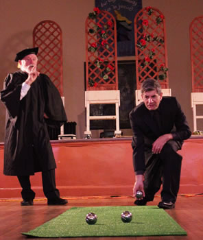 Holofernes in an academic gown and morter board with a finger up to his lips and his left hand on his hips talking as Nathanial kneels on one knee to cast a metal ball down an Astroturf rug where two other balls already sit: in the background, on a stage  are trellises of roses on wheeled countertops