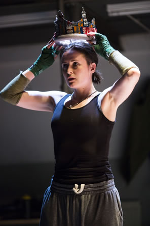 Hal in black tanktop and gray sweats, with green fingerless gloves and an olive green sleeve on the elbow of her right arm, lifts a crown made of aluminum drink cans onto her head.