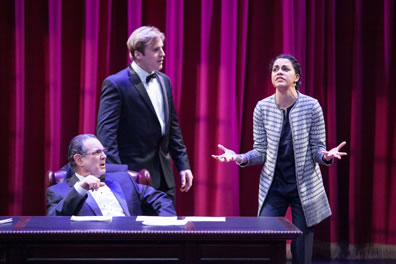 Scalia in a black tux sits at his desk with Brad, also in a tux, standing behind them, both looking past Cat in a long, black-and-gray-striped sweater and dark gray blouse and pants, her hands outstretched in agitation.