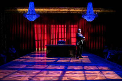 Scalia in a dark suit and tie stands at one end of his large oak desk with leather chair  at the center underneath one of two chandeliers on a stage with the light coming through paned windows casting shadows on the parquet stage and red curtain in the background.