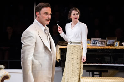 Teck in cream jacket and tie with white shirt stands attentively as Marthe in the background smokes a cigarette next to the piano
