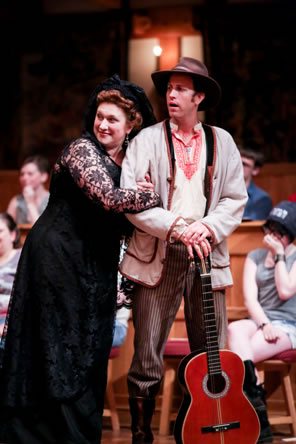 Olivia in black dress with lace sleeves and black hat leans against Feste with her arms in his as he stand wearing a hobo hat, simple jacket, Illyrian folk shirt and striped pants, his guitar standing on the floor with his hands folded on the key end. Audience on gallants' stools in background.