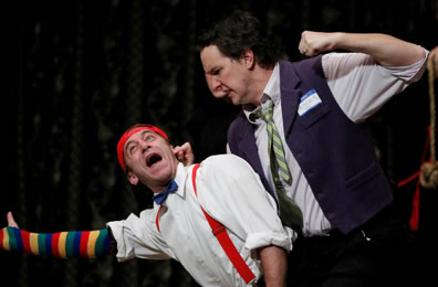 "John Harrell as Antiphous, fist raised and holding the ear of Tyler Moss as Dromio: Harrell in vest and tie with a ""Hi I Am Prisoner"" convention badge, Dromio in red suspenders, bowtie, and multi-color stocking on his right arm"