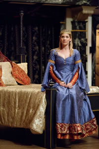 Alais in a rich blue gown sits on the end of a bed in The Lion in Winter