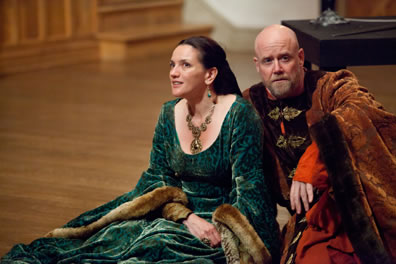 Eleanor in green dress and Henry in red fur robes sit on the Blackfriars stage in The Lion in Winter