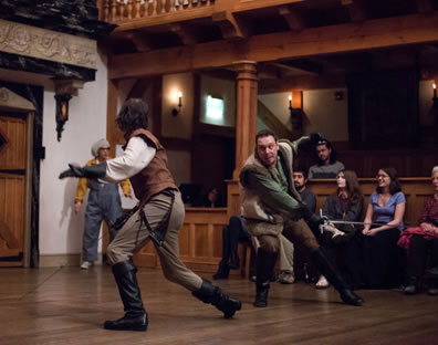 Sword fight with characters, both in vests and knee-high boots; servant in overalls in the corner, and members of the audience behind.