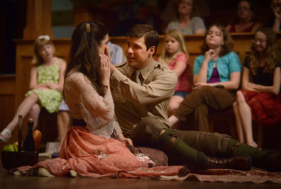 Bertram in mid-20th century british military uniform--khaki shirt and tie, brown pants, olive stockings, brown boots--sits on the floor and has his hands up to Diana's cheek as she has her right hand on his; she's in colorful print lacey blouse and peach dress.