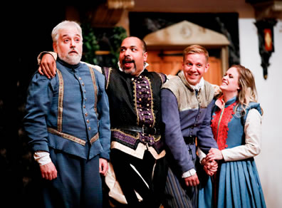 Leonato in blue renaissance uniform jacket and pants with gold trim, Don Pedro with his arms around everybody and wearing black and purple renaissance short jacket and breeches, Claudio laughing and wearing a purple jacket, striped pants and black belt with tan shoulder shawl, and Hero holding his hand and wearing a blue dress with red trim on the front and white shirt.