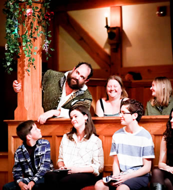 Benedick in green renaissance vest jacket over white shirt leans out from behind a vine-covered post next to two laughing women with three kids on the gallant stools in front of him, one boy looking up at him.