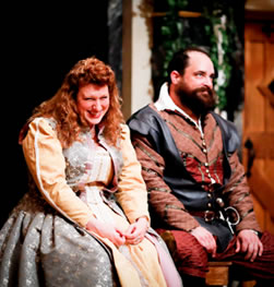 Beatrice in ornate yellow and silver dress, ands on her lap and snickering as she looks down to the right, next to her Benedick in black vest over rust and burgundy colored renaissance jacket and breeches, rolling his eyes looking up and to the left, both sitting on a bench