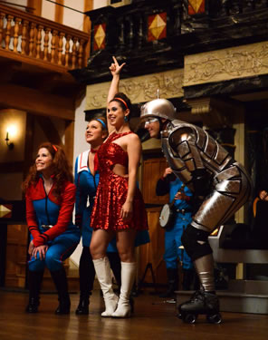 Miranda in a metalic red dress and white go-go boots with arm upraised, Gloria in red and aqua flight suit crouched down, Glenzer bent over, and robot-dressed Arial bend over, too.