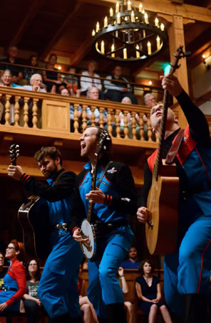 The three wear blue jumpsuits with red trim, and the audience of the wooden Blackfriars is sittein on the stage and in the galleries in the background.