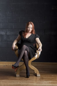 Fallon in black dress and sheered pattern stockings with red-sole heels sits in a lord's chair, a crown in her hand.