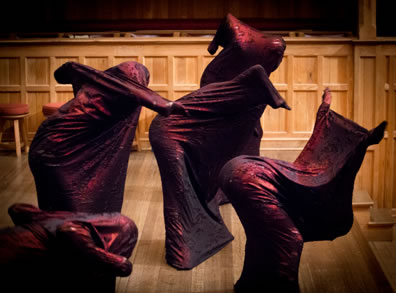 Five demons in their tight sheets bend in various configurations on the wood paneled stage