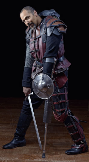 Richard dressed in red and black leather over chain mail armor, a single cructh with a small shield on his left hand, his sword in his right hand pointed down to the floor, his head tilted forward from the armored hump in his back