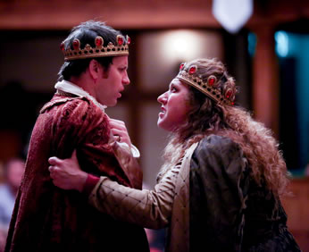 Margaret grips Henry's arms as she lectures him, he pensively looking back with his hands folded with insecurity at his breast, he in red velvet cloak, she in purple cloak, both with gold crowns sporting red rubies.