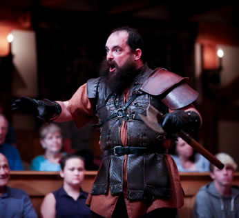 Cade in leath armor over a worker's tunic, black gloves, and a huge beard as he holds a stick and roars with eyes bulging. Audience sits in the background.