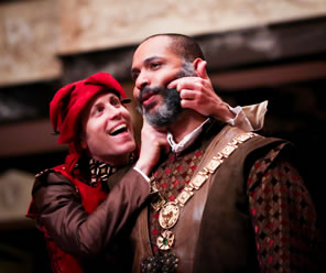 The Fool in red jesters cap, brown shirt, red vest, and colorful collar uses his fingers on Lear's bearded cheek to make him smile as Lear stares vacantly ahead, wearing regal shirt, brown leather vest, and a medallion on a chain.