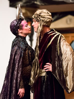 Titania in black glittery gown and silver horns on a 20s black cap stares breast to breast at Oberon in blackand purple robe, gold cape, and gold turban, with his hands on his hips