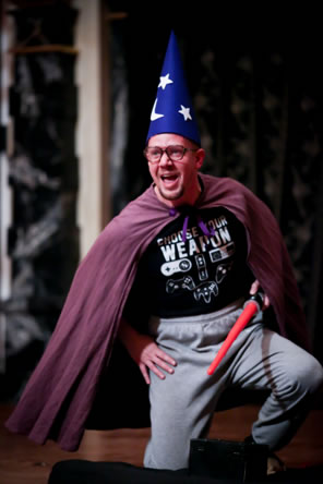 "Arragon on one knee, blue star and moon wizard hat, brown-framed glasses, purple cape, ""Choose Your Weapon"" black t-shirt, gray sweatpants, and red light saber in his left hand, right hand on hip."
