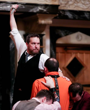 Shylock in black vest, white shirt, and black and white-striped tie holds his knife aloft but looks off to the side toward Portia, his hand on the orange-prison-garb clad Antonio (back to us) as Bassanio and Gratziano, heads down, brace Antonio.