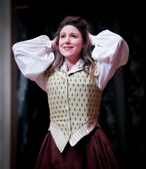 Judith, in simple Elizabethan waist jacket, blousey shirt and maroon dress holds her hands up to her head in wonder.
