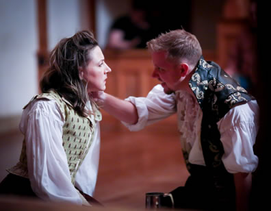 Sitting on the stage, Burbage in floral vest, unbuttonned over puffy white shirt, faces Judith with his hand on her left shoulder, she dressed in simple Elizabethan waistcoat and dress.