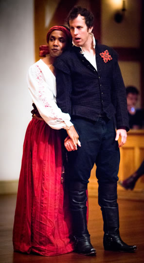 Flamineo stands in blue rennaissance short jacket, trousers, and kneehigh black boots with a red badge on his left lapel, and Zanthe in simple white blouse with floral embroidery and floor-length pleated red skir rests her head on the back of Flamineo's shoulder and holds his hand.