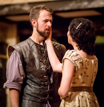 Leantio is wearing a leather renaissance  vest with buckles down the front and a purple shirt with rolled up sleeves. Bianca in simple tan dress with a pattern of brown brances and leaves holds her right hand on Leantio's bearded cheek.