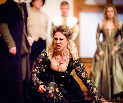 Livia in black dress with floral sleeves and skirt and gold lace high collar screams as she kneels on the floor, other characters standing in the background