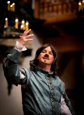 Cyrano with right hand upraised and wearing a blue jacket with frilly cuffed white shirt, shoulder-length hair