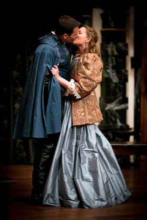 Christian in long blue soldiers coat and black boots kisses Roxane, who is gripping his sleeve, wearing a long blue dress and tapestry-like brown jacket with puff shoulders
