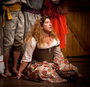 The Jailer's Daughter, in country patterned Elizabethan dress, kneels on the floor looking up in distraction with the legs of the Morris dancers behind her.
