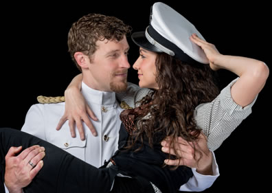 Benedick in old-style formal navy uniform carries Beatrice, wearing his hat and a black vest and pants with pinstriped shirt.