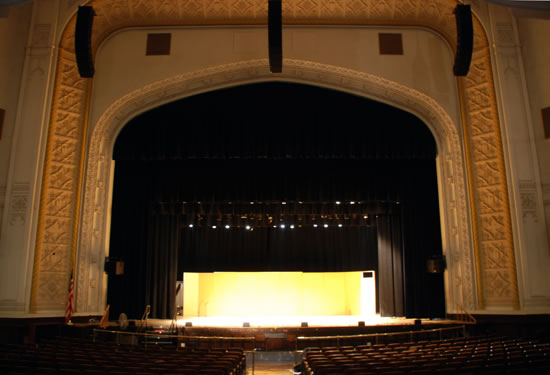 Brooklyn Tech High School auditorium with a light glowing from the back of the stage