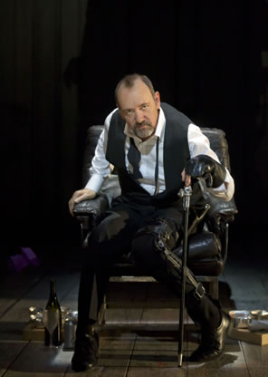 Kevin Spacey as Richard sitting in a chair with cane in left hand