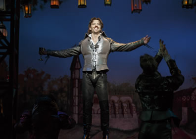 In gun metal gray leather jerkin, shirt, pants, and large codpiece, Shakespeare stands with arms outstretched--goblet in right hand--taking in the adulation of the crowd (we can see a silhouette of an applauding fan to the right)