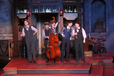 On the three-step platform of the speakeasy set, the musicians in vests and bowties sing, Dull with his standup bass, Costard holding his trumpet