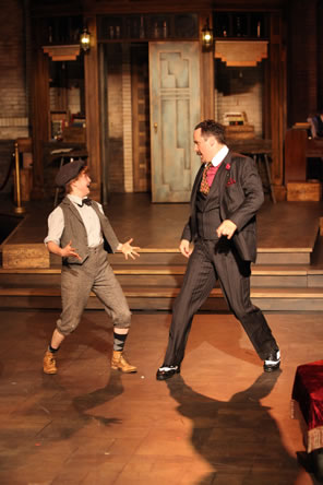 Moth in newsboy cap, brown vest and brown knee-pants with stockings and bowtie dancing with Don Armato in dark gray pinstriped three-piece suit with red-dotted cravat and rose boutineer; the speakeasy set is in the background.