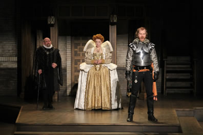 Cecil in black cloak with ruff collar, Elizabeth in gold dress with white trim, gold embroidered corset and jacket with high, spread-out collar, Essex in armor and black pants