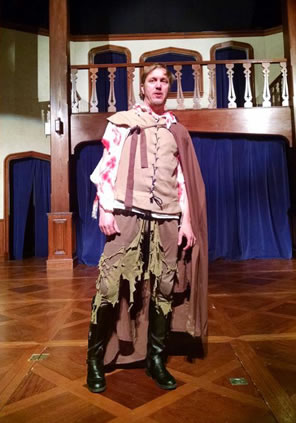 Shakespeare in Elizabethan tunic and kneepants, which are n tatters, blood on his shirt sleeves, cape and black boots