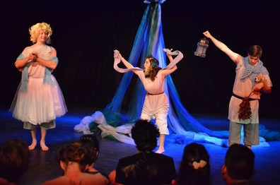 Flute as Thisbe wears a ballerina dress over his shin-length pants and bare feet, a blue scarf draped around his arms, and a blond wig with hands clasped together; Snug as Lion has her hands raised holding the mantle across the back of her neck, flowers in her hair; Starveling as Moonshine holds up the lantern in his right hand, holds a stuffed dog in the crook of his left arm and holding a thorn bush in that hand, his head down.  We see the backs of the noble audience's heads. Maypole is in the background.