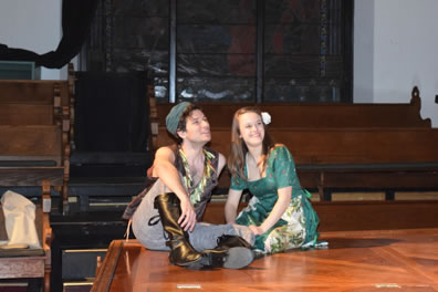 Florizel and Perdita sit on a stage floor, with church pews in the background. he's dressed in flower brown vest, gray work pants and brown boots and wears a simple gray cap. She's wearing a floral green dress and has a white carnation in her hair.