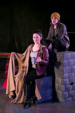 Hallie in red leather jacket, t-shirt, black pants and black boots with a brown cloak and holding a tankard sits on a block while Peto in yellow stocking cap, brown jacket and black jeans sits cross-legged on a stack of stone-wall painted blocks