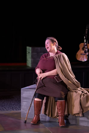Giant-bosomed Jill Falstaff in red knit blouse, brown skirt with black leggings underneath, brown boots, and brown cloak, sits with a cain in her hand.