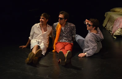 Sitting on the floor are Romeo in white shirt, unbuttoned to the chest and white shorts, Mercutio in sunglasses, orange pants, purple print shirt and orange scarf, and Benvolio, also weareing sunglasses in a blue striped hoodie and shin-length pants