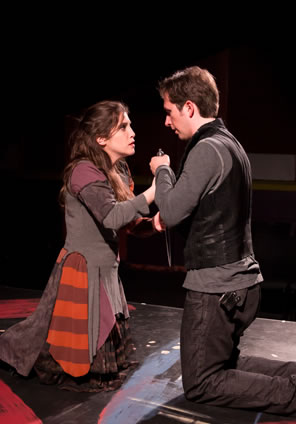 Annabella in gray tunik, purpe sleeves and red-striped panels of fabrick over a black print dress kneels opposit Giovanni in black leather vest, black jeans, and grey sweatshirt, both clasping a dagger between them.