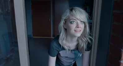 Sam, straggly blond hair, patterend athletic tee-shirt, is looking up outside a window, a look of wonder on her face, and in the background is a room with a door.